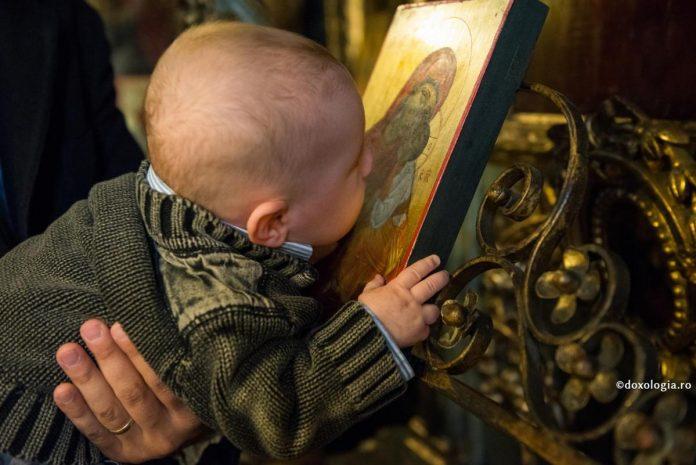Copil care sărută icoana